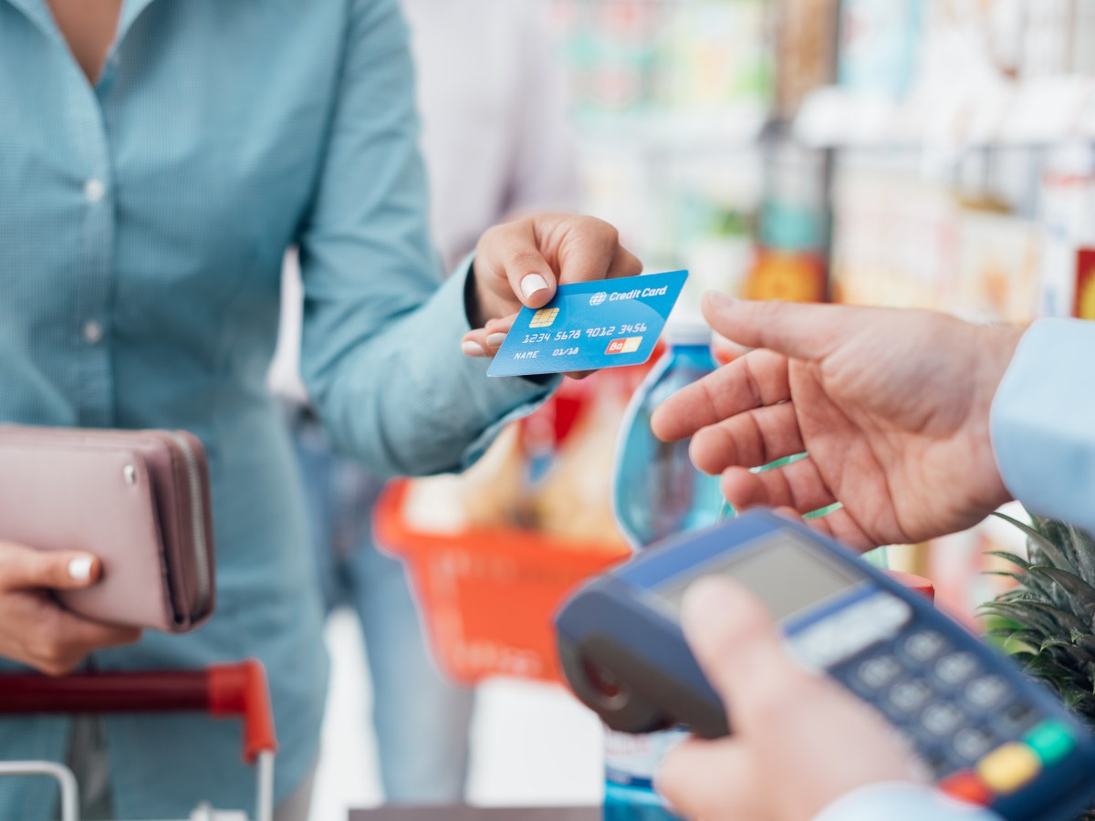Woman,At,The,Supermarket,Checkout,,She,Is,Paying,Using,A