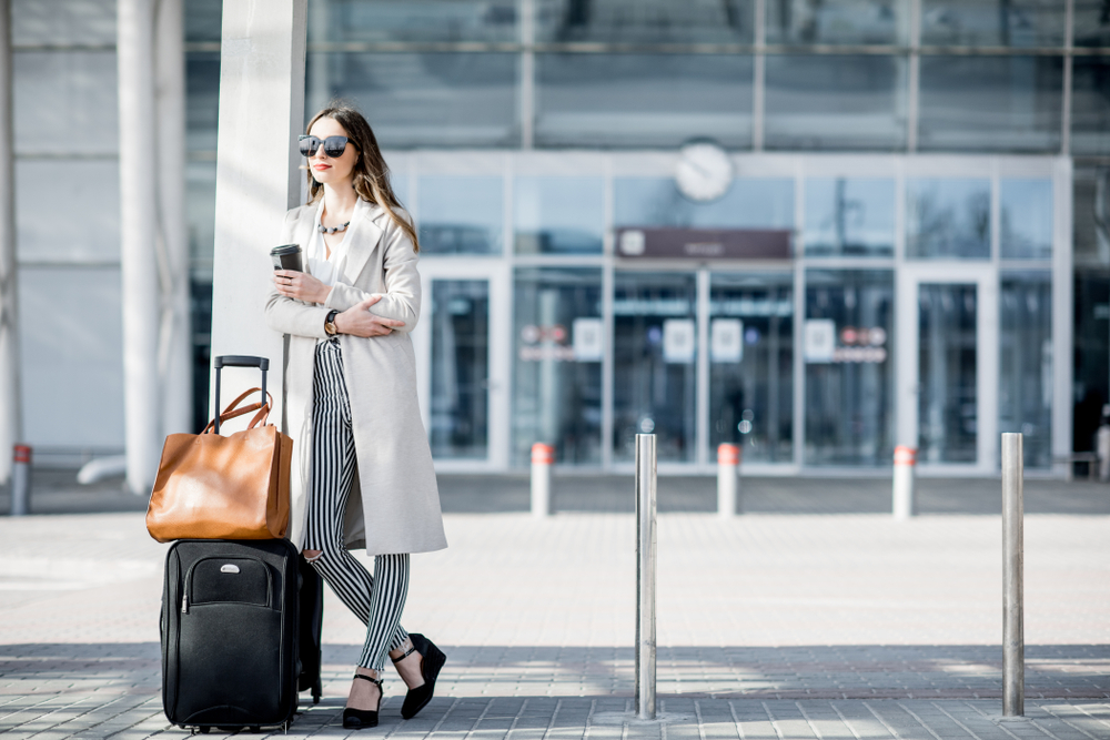 Business,Woman,Standing,Near,The,Airport,With,Luggage,During,The