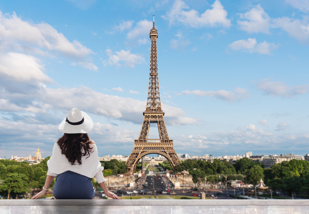 Young,Traveler,Woman,In,White,Hat,Looking,At,Eiffel,Tower,