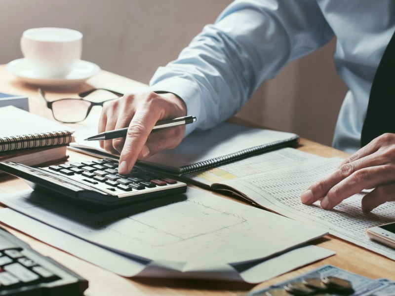 Businessman,Working,On,Desk,Office,With,Using,A,Calculator,To